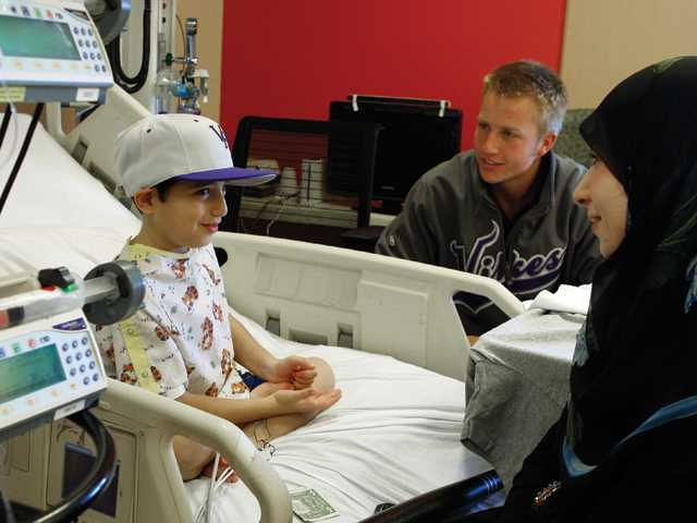 Hassan Saleh, 9, who has a heart muscle disease known as cardiomyopathy and is awaiting a transplant, with his mother Liliana gets a visit from Valencia baseball catcher Brian Mundell at Children's Hospital Los Angeles on Tuesday. Mundell, one of the top 150 baseball prospects in the U.S., will represent CHLA and baseball fan Saleh in the upcoming Home Runs That Help Power Showcase, a home run and skills competition in Phoenix on Dec. 27-29.