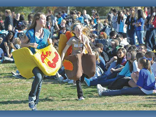 Rio Norte Junior High School seventh graders Gracie Rusk, left, and Julie Smith, dressed in their Turkey Bowl costumes, run up and down the sidelines during the ninth annual Turkey Bowl football game among eighth graders at Rio Norte Junior High School in Santa Clarita on Wednesday.