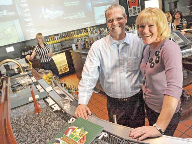 Owner Tom Law and wife Jodi Law pose for a photo at Gameday Sports Grille & Bar in Valencia.