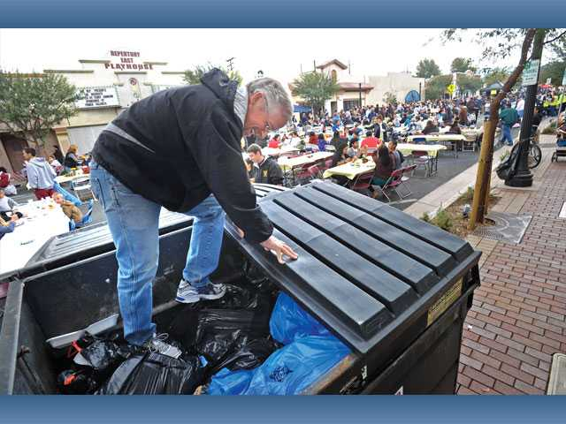 Volunteer Pat Downing compresses bags of trash in a bin at the Newhall Bicycle Co.'s annual Thanksgiving Feast in Newhall on Thursday.
