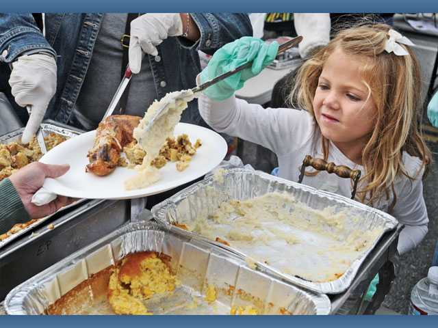 Charlotte Curtis, 6, serves mashed potatoes at the Newhall Bicycle Co.'s Thanksgiving Feast in Newhall on Thursday.