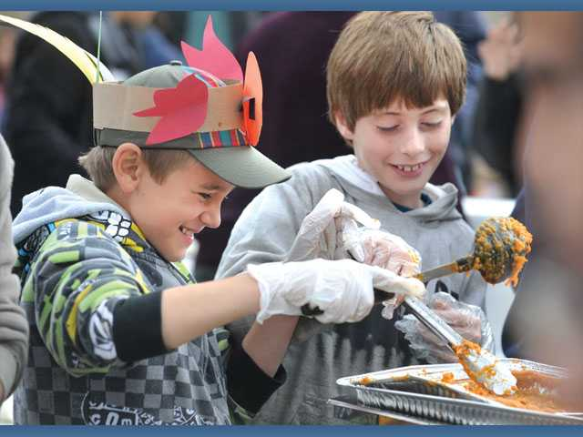 Volunteers Carson Messick, 9, left, and Dominic Riccardi, 9, stir sweet potatoes in the serving line.