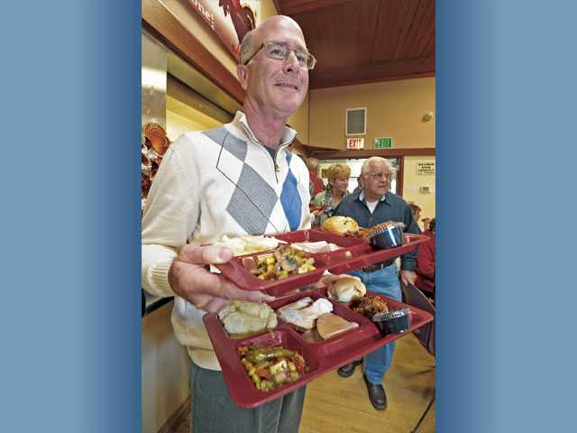 Volunteer Marc Gale, of Canyon Country, carries two meals to serve at the Santa Clarita Valley Senior Center Thanksgiving day feast in Newhall on Thursday.