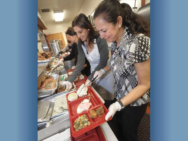 From left, Karen Roberts, Susan Lawrence and Carmen Gahan prepare trays of turkey and mashed potatoes.