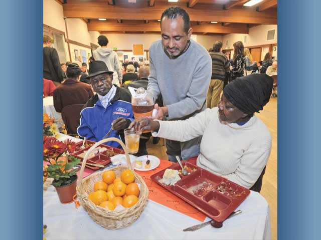 Volunteer Sam Ochoa, center, pours cider for Wilson Mwaoloziri and Emily Lowlewlo at the Thanksgiving feast.