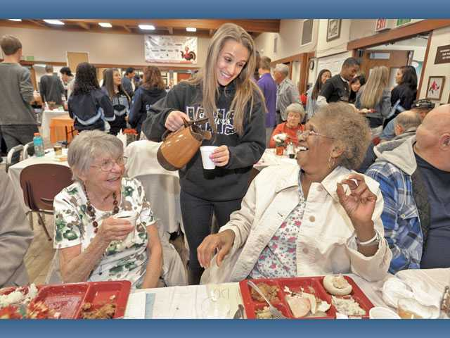 Gigi Sarnicola, 17, center, pours coffee for seniors Fern Bridgeman, left,  and Esther Drayton at the Santa Clarita Valley Senior Center Thanksgiving feast in Newhall on Thursday.