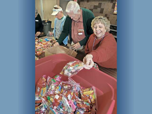 Volunteer Diana Flittner, right, of Santa Clarita, bags candy with other volunteers in Valencia.