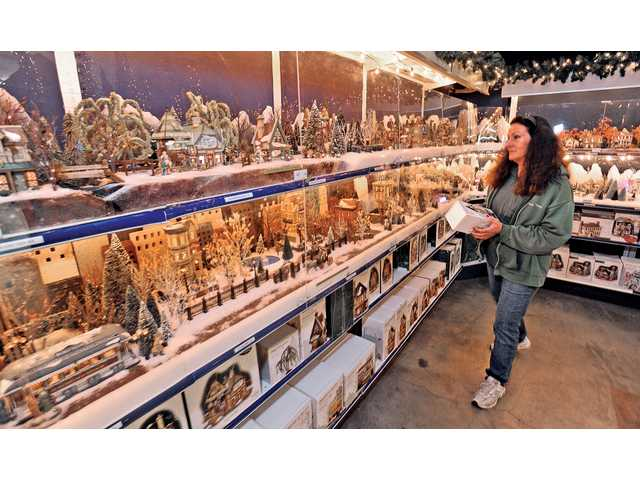 Department 56 section manager  Laura Gullas views the display of miniature Christmas buildings at Green Thumb International in Newhall.