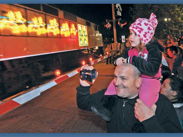 Randy Wolff holds his daughter Madison, 2, on his shoulders as the Holiday Toy Express rolls into the Jan Heidt Newhall Metrolink Train Station on Sunday night.