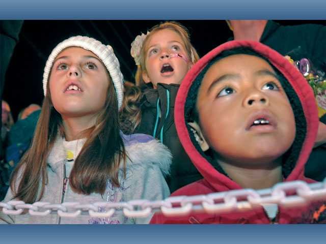 From left, Faith Abt, 7, Lily Thompson, 9, and Roman Vivian, 4, watch an alien character sneak up on Santa during the show.