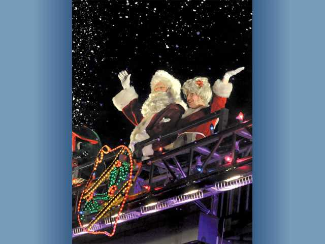 Snow flies into the crowd as Santa and Mrs. Santa wave from the Holiday Toy Express.