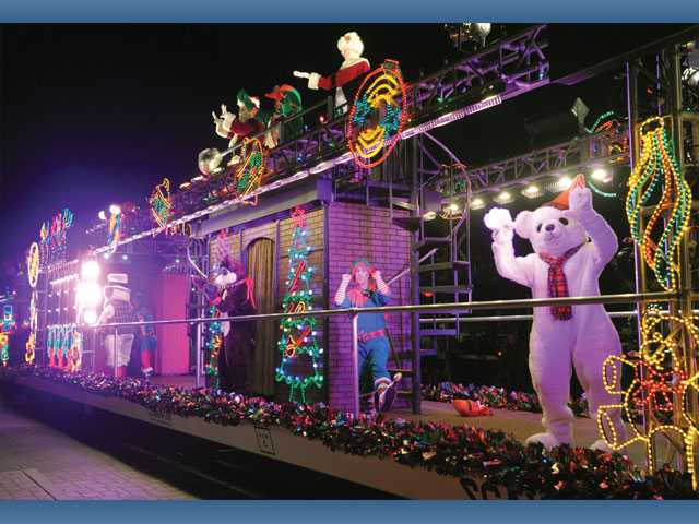 Characters dance below as Santa and Mrs. Santa wave to the crowd from the Holiday Toy Express.
