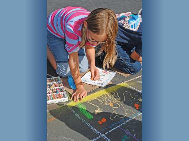 Lucy O'Brien draws a squid at Highlands-Emblem Elementary School's Chalk Festival.