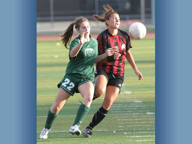 Hart's Kelsey Steck, right, tries to control the ball and fend off Thousand Oaks' Natalee Dueber on Tuesday at Hart High School. The Indians tied the Lancers 0-0.
