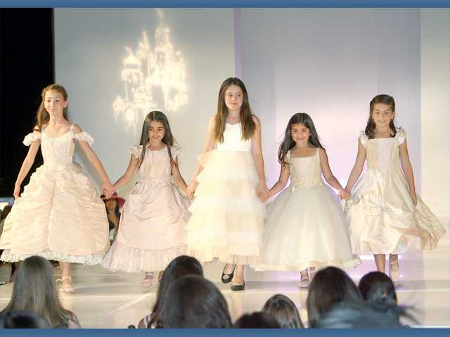 "Young ""princesses"" model fashions by Belle of the Ball. (Far right) An elegant gown walks the runway worn by a professional model and escorted by an Afghan hound."