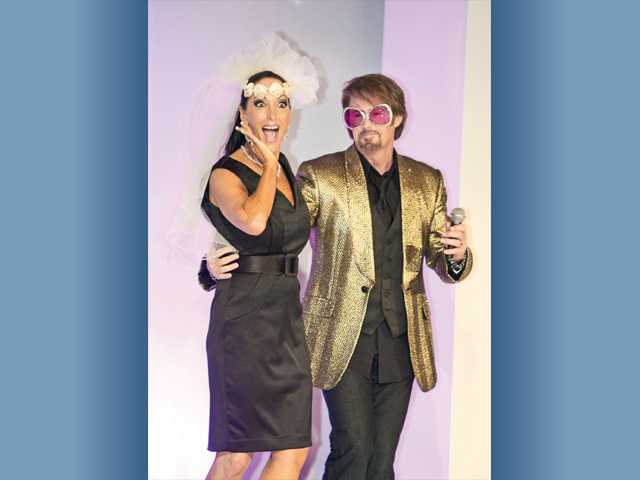 "Shelley Hann, left, chairwoman of A Royal Fashion Show, is escorted down the runway to the song ""Chapel of Love"" by emcee Ed Masterson sporting his ""Elton John"" look."