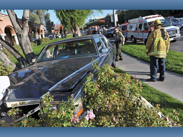 Authorities work the scene of a solo vehicle crash at the northeast corner of McBean and Magic Mountain parkways in Valencia on Wednesday.