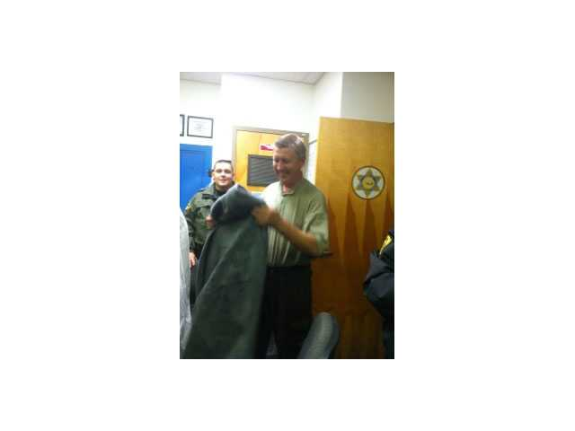 Happy to be solid ground, blanket in hand, Alexander Vajilyev, 60, accepts a blanket from his rescuers - deputies with the Parks Bureau of the Los Angeles County Sheriff's Department.