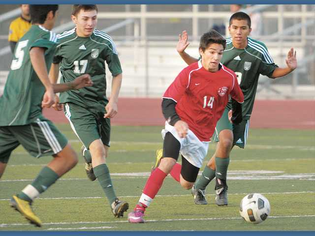 Hart's Nico Ferrero (14) dribbles through the Moorpark defense on Thursday at Hart High School.