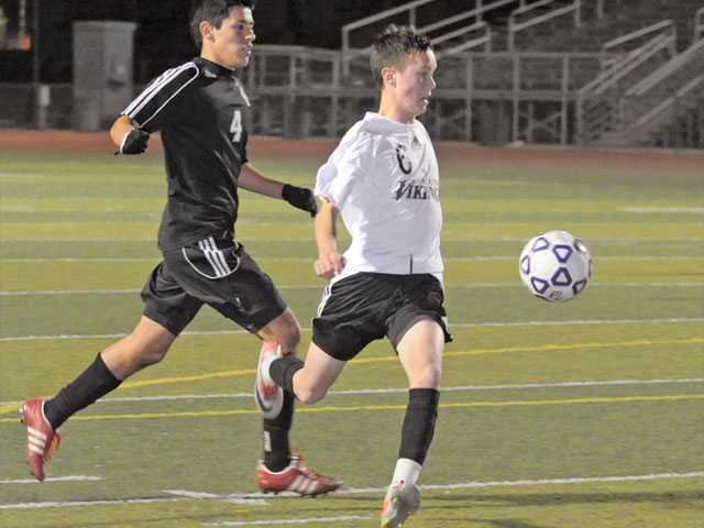 Valencia's Zach Klindworth (6) charges the goal with Stockdale defender Santos Mendieta on his back on Friday at Valencia High School.  Klindworth scored two goals in his team's 3-1 victory.