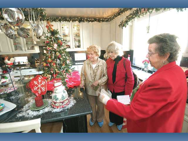 Sharlot Sheets, left, and Barbara Huffline listen as home tour hostess Joanie Stanzione, right, describes the Christmas decorations in the kitchen at the Hall residence. Funds raised from the event will benefit the hospital's new neonatal intensive care unit.