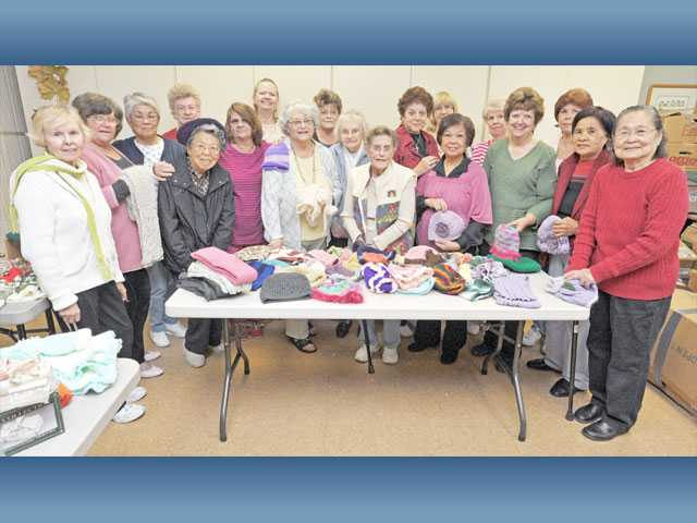 Members of the needlework class hold scarves and hats destined for the military and children in need at the Santa Clarita Valley Senior Center in Newhall on Nov. 28.
