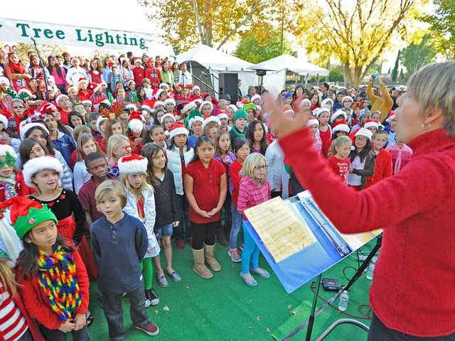 Jami DeSiena leads the Newhall School District Choir at the  Community Tree Lighting Celebration at Henry Mayo Newhall Memorial Hospital on Sunday. The choir includes students from grades three through five from all 10 elementary schools.