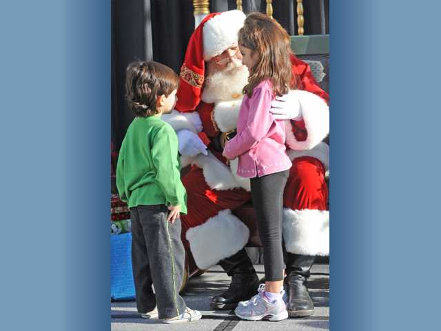 Santa Claus visits Leila Azodi, 6, and her brother Logan Azodi, 3, who tell him what's on their lists.