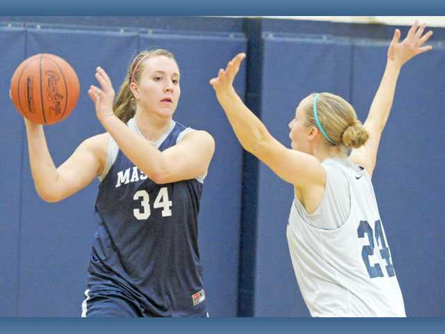 The Master's College's Lindsey Levanen (34) looks to pass as Kimberly Iverson defends during practice at Bross Gym on Monday. For various reasons, the Mustangs have had to replace three starters so far this season.