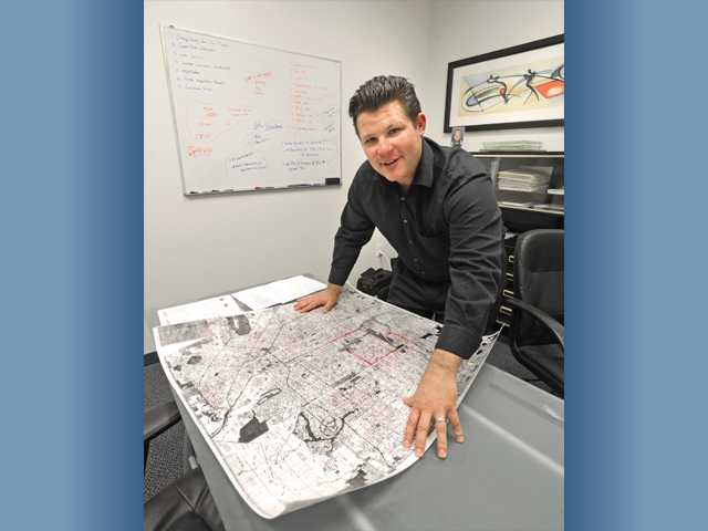 Matt Skinner of Twelvestone Capital Group unrolls a map in his new Valencia office on Nov. 30.