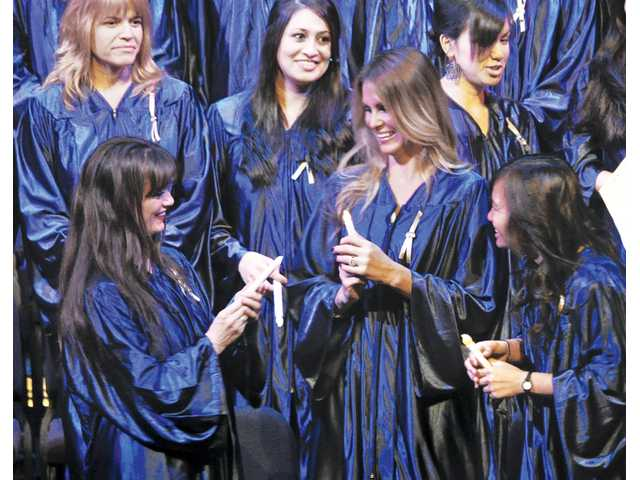 "Graduating registered nurses, front row from left, Shannyn   Marlen, Tracy Erickson and Michelle Saldevar ""pass the flame"" using electric candles during the candle-lighting ceremony at the Santa Clarita Performing Arts Center at College of the Canyons Valencia campus."