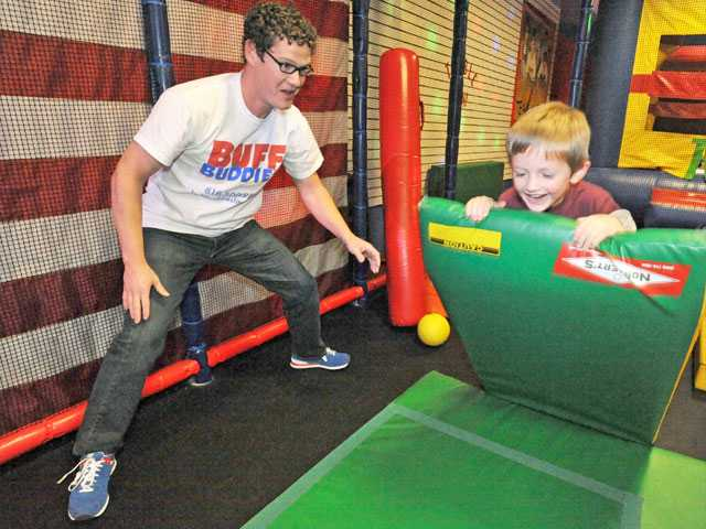 Scottie Bahler, vice president of operations, left, encourages Luke Clendening, 4, as he plays in an obstacle course at Buff Buddies at Westfield Valencia Town Center.