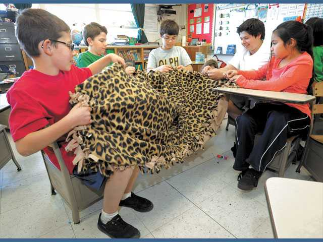 Our Lady of Perpetual Help students, from left, fourth-grader Pierce Thomsen, seventh-grader Aidan Brown, sixth-grader Alex Bordbar, eighth-grader Kevin Wheeler and third-grader Grace Alcedo assemble a blanket for the homeless, at Our Lady of Perpetual Help School in Santa Clarita on Friday.