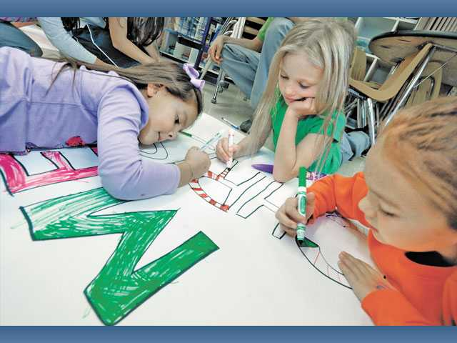 Our Lady of Perpetual Help School students, from left, kindergartner Ryan Nunez, first-grader Laney Grider and third-grader Destiny Segura color in the letters of a Merry Christmas greeting on the wrapping paper for a blanket for the homeless.