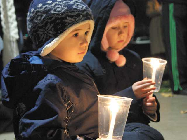 Ashley, 3, and Lorenza Reniker, 11, hold candles at a ceremony at Canyon Country Park on Sunday.