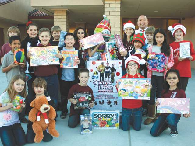 West Creek Academy kids pose at the school with the toys they collected for the Spark of Love Toy Drive. The kids and their families drove to Westfield Topanga Mall to drop off new, unwrapped toys and sports equipment and perform holiday songs.