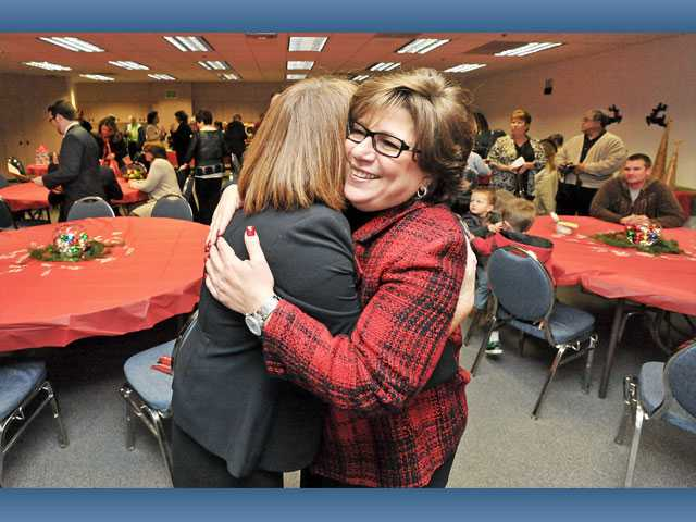 Michelle Morse, director of child care for the Saugus Union School District, left, and school board member Rose Diaz embrace at Diaz's farewell reception in Valencia on Tuesday.