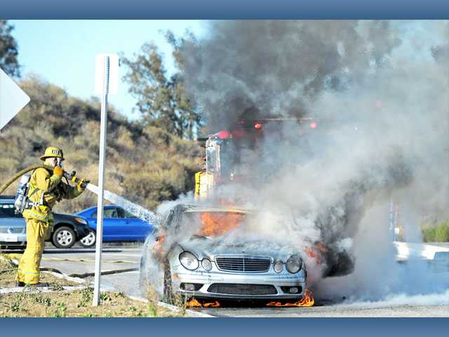 A firefighter knocks down flames engulfing a Mercedes-Benz sedan on Santa Clarita Parkway south of Newhall Ranch Road in Santa Clarita on Wednesday. The car's driver pulled onto the road after noticing smoke under the hood and escaped without injury.