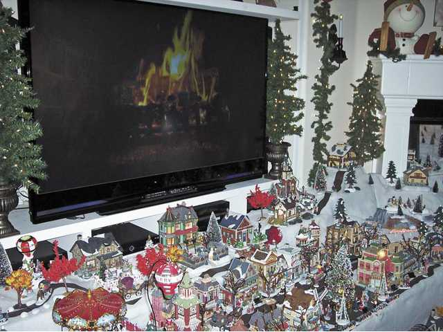 A warm fire blazes away on the flatscreen TV above miniature Christmas villages at Mark and Carla Caple's house in Saugus. Mark's brother Thomas Caple also has an extensive village display.