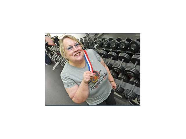 Results Fitness client Carol Morton holds up the gold medal she won at her first power-lifting competition.
