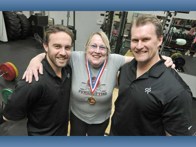 Morton with Results Fitness coaches Brian Gilbert and Craig Rasmussen.