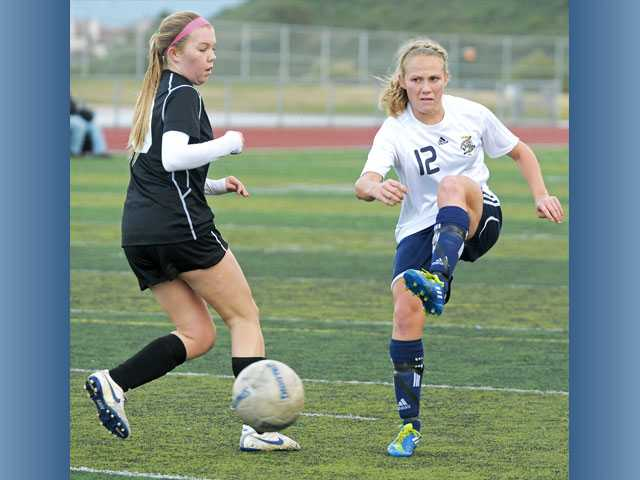 West Ranch forward Hailey Reynolds (12) fires a shot past Ventura's Paige Wagner on Thursday at West Ranch High. Reynolds scored and the Wildcats won 3-0.