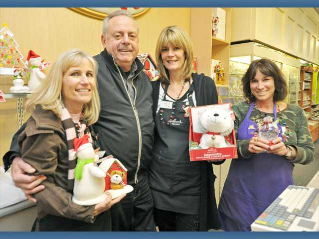 Left to right, Lori Tucker, John Trimble, Sue Savigar and Stacie Allegra display a variety of holiday items available at Lee's Hallmark.