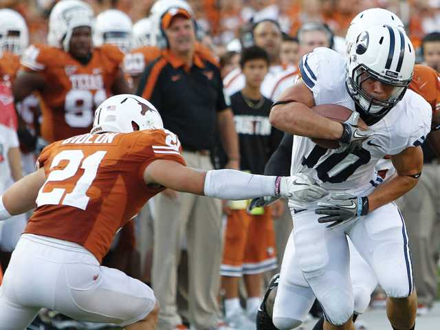 Canyon graduate J.J. DiLuigi (10) tries to dodge Texas safety Blake Gideon Sept. 10 in Austin, Texas. DiLuigi could become the 10th player in BYU history with 1,000 career rushing yards and 1,000 career passing yards.