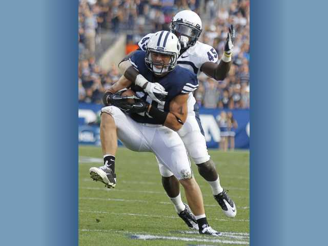 Canyon High graduate and BYU running back J.J. DiLuigi, front, drags Utah State tackler Maurice Alexander during the first half on Sept. 30 in Provo, Utah. DiLuigi has been a productive back during his BYU career.