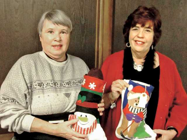 From left, Sonia C. Stodden and Santa Clarita Valley Senior Center Supportive Services Director SuzAnn Nelsen display two of the 23 specially-made-and-filled holiday stockings that Stodden and her husband, Phillip, have prepared this season for homebound seniors.