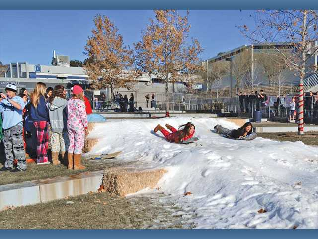 Saugus High School students Madeline Moya and Melissa Morales sled at their high school on Friday.