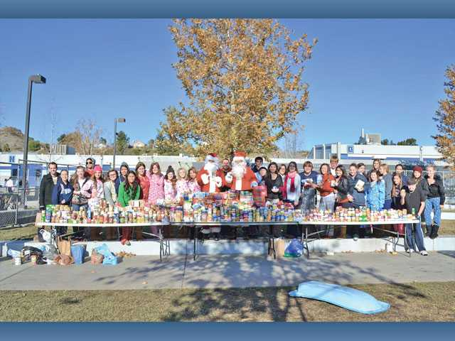 Saugus High School students show off their food donations as part of a snow day on Friday. The school's student government brought in 14 tons of snow and students who donated to the SCV Food Pantry were able to play in the snow.
