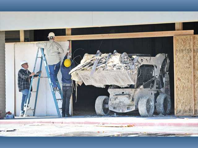 Workmen put up walls as a loader moves debris from the old Mervyn's store in the River Oaks Shopping Center on Friday.