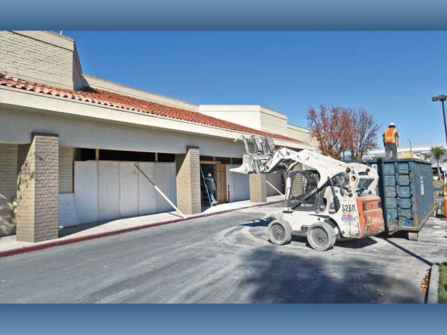 Workmen put up temporary walls as a skip loader moves debris from the interior of the store as construction continues to renovate the old Mervyn's store in the River Oaks Shopping Center on Friday